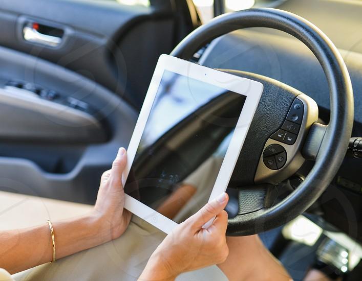 woman using ipad in car photo