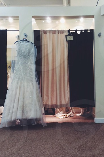view of white dress hanging on the wall photo