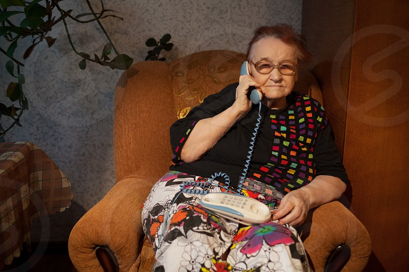 Old woman talking on the home phone sitting in the arm-chair in the evening photo