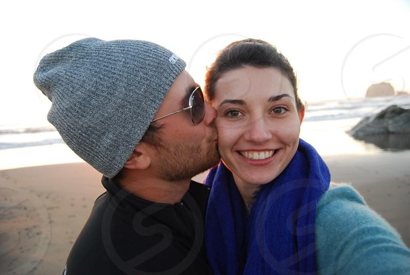 man kissing woman on beach photo