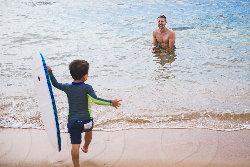 Father and son enjoying the gentle waves on Hawaii's beaches. photo
