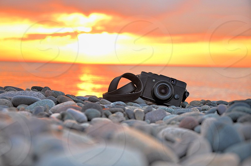 black camera with strap on pebbles photo