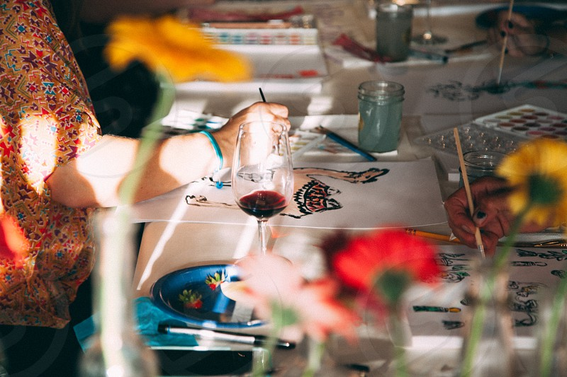 person painting beside clear long stem wine glass photo