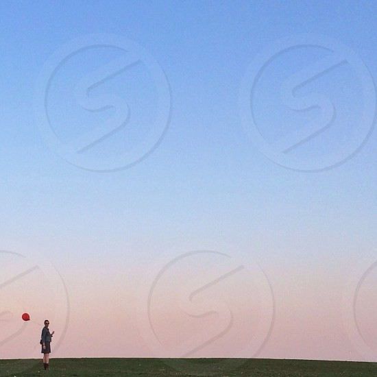 woman holding red rubber balloon photo