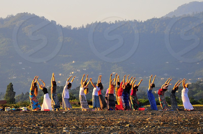 group of women doing yoga outdoors photo