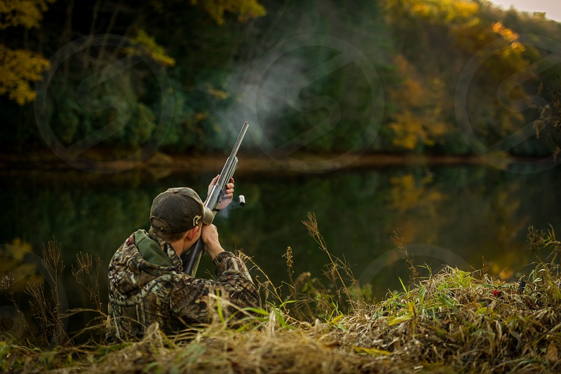 men wearing black gray and brown camouflage jacket using a shotgun aiming on top near body of water during daytime photo
