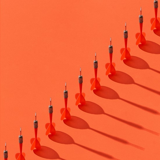 Vertical darts in a diagonal line with shadows on an orange background copy space. photo