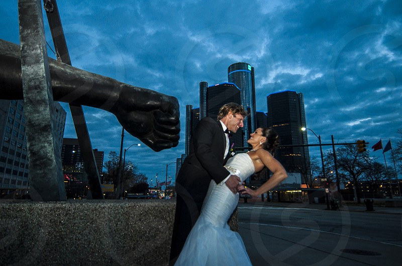 man and woman in wedding attire embracing at night near statue of man's fist photo