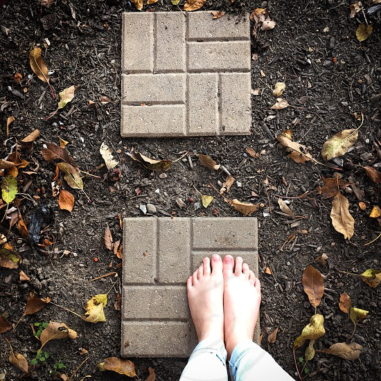 Feet brick leaves dirt gravel nature squares stone cement outside photo