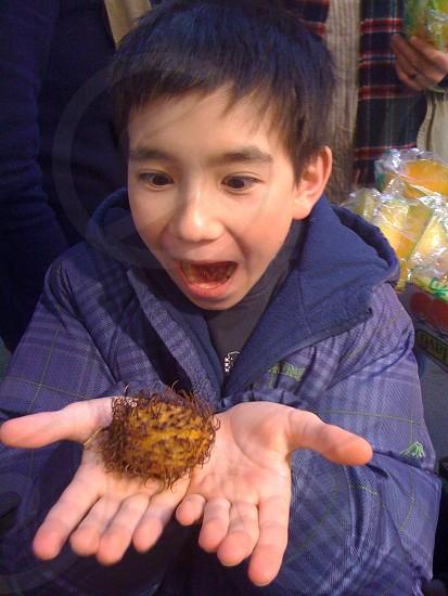 boy with black hair holding yellow rambutan photo