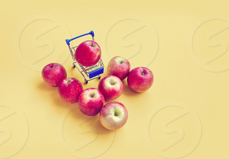 Red apples with mini shopping cart with yellow vintage color theme instagram color style with copy space or text space photo