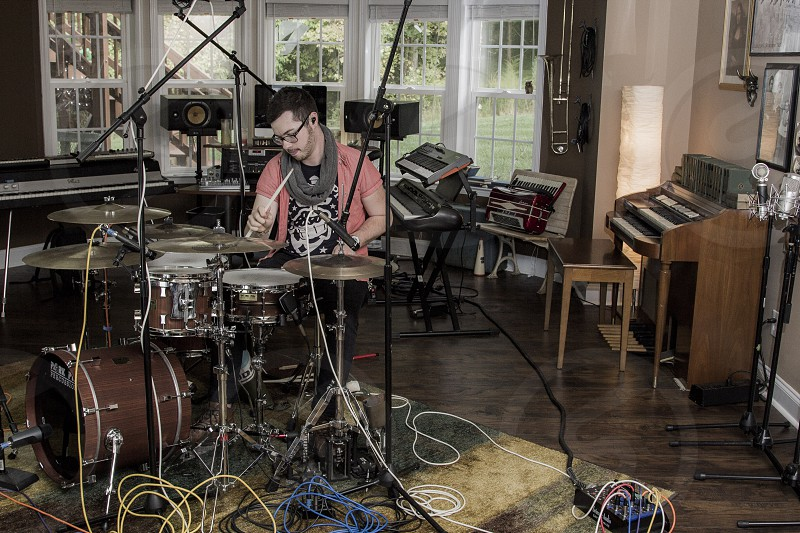 man playing drums inside house photo