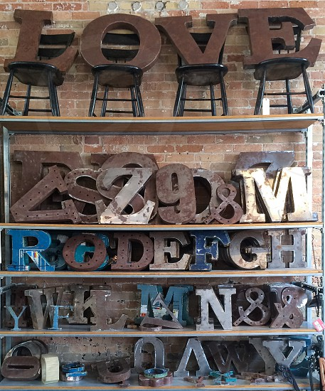 brown wooden love sculpture on top of cabinet along with other carved letters photo