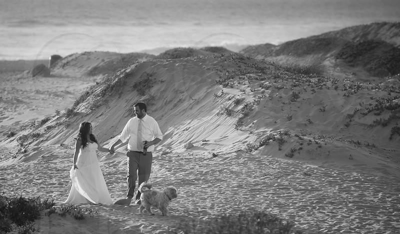 Happy Newlywed Couple Walking the Beach photo