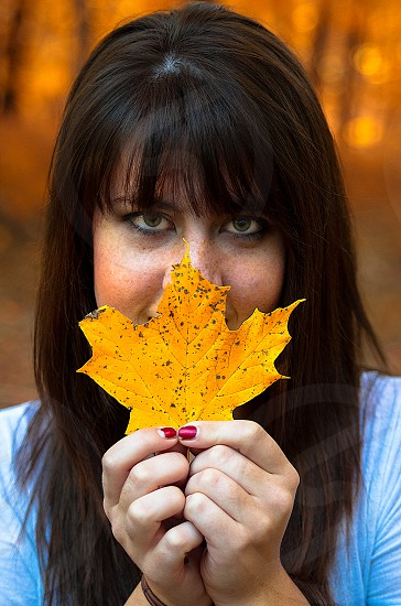Girl with leaf in face. Pretty eyes. Golden leaf. Fall photo