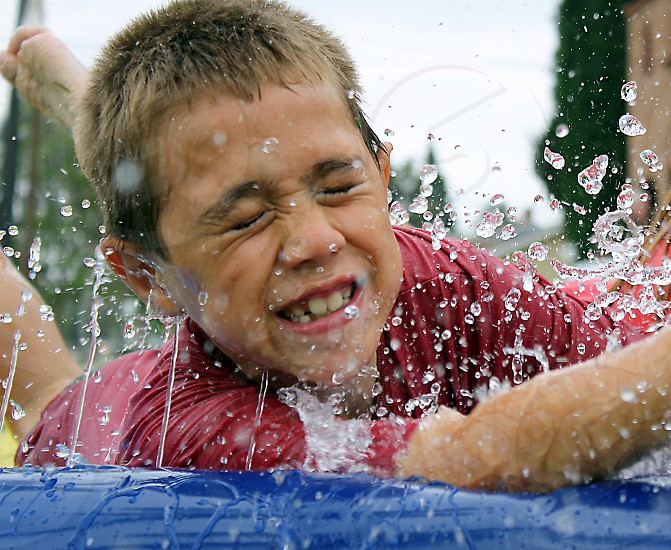 Close up of a little boy sliding on his stomach as water splashes in his face. photo