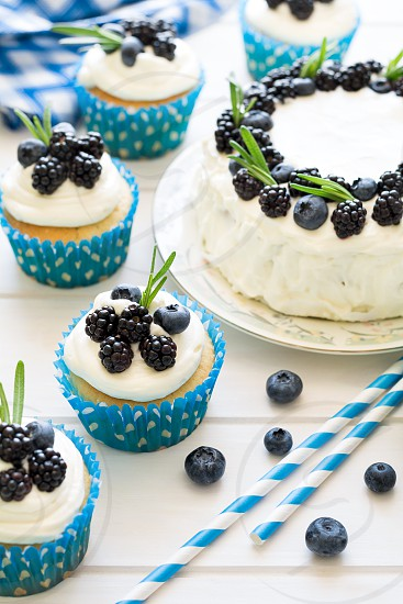 Homemade cupcakes with frosting blueberries blackberries and rosemary leaves photo