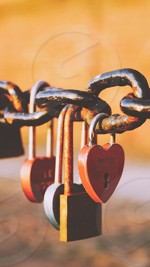 close up photo black brass and red lovelocks on the black chain link photo