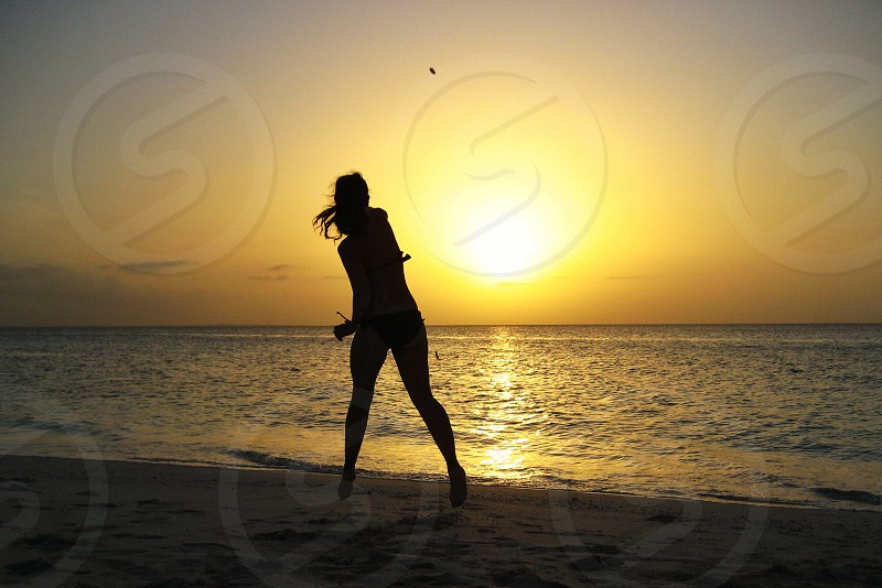Beach summer sunset girl throwing rock photo