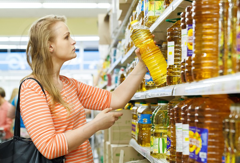 Young woman buys sunflower oil in supermarket photo