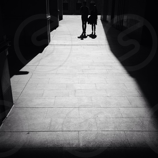 silhouette of two people walking on pathway during daytime photo
