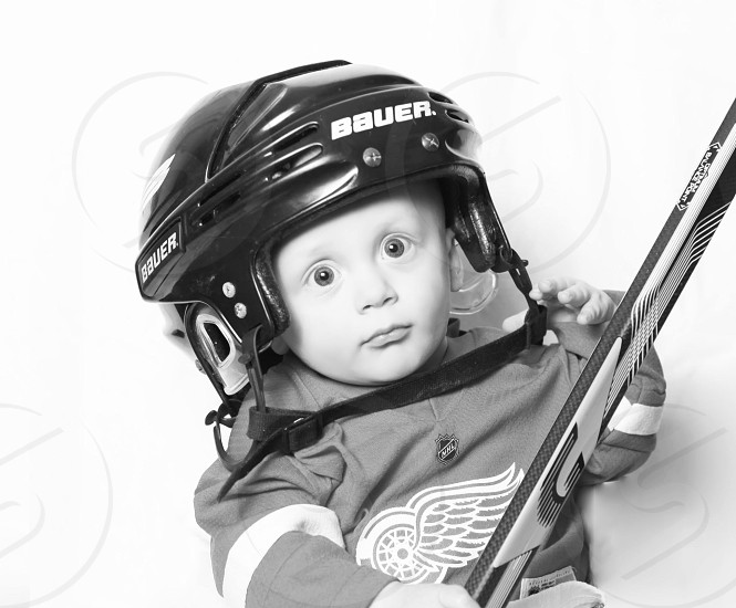 baby wearing a black hockey helmet and uniform photo