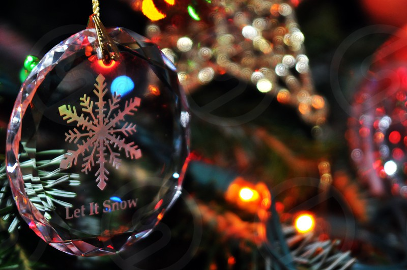 Glass Let It Snow snowflake holiday ornament on a Christmas tree photo
