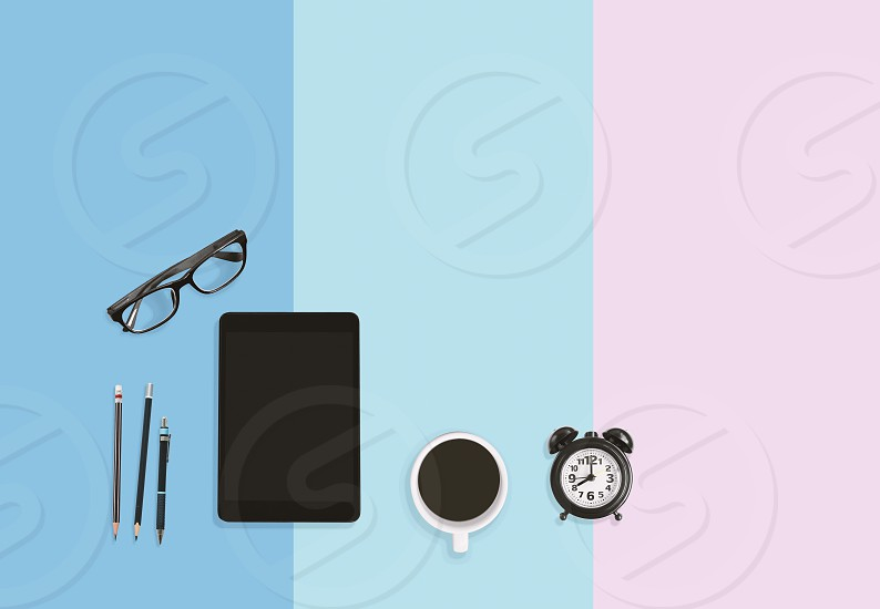 Modern home office working area concept Black alarm clock A cup of black coffee eyeglasses pencils and tablet on sweet pastel background with copy space photo