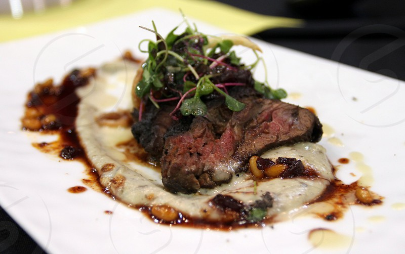 Sirloin steak over mashed potato and gravy puddle with microgreens photo