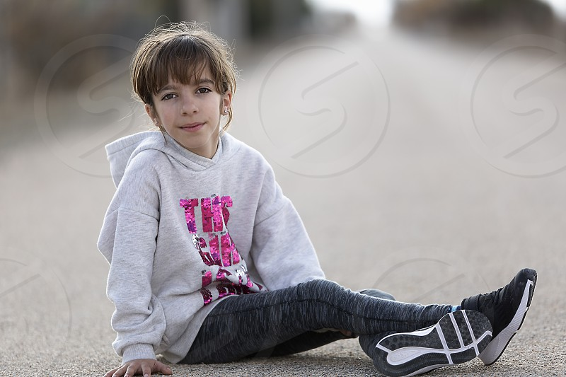 10-year-old girl sitting on the floor of a car looking at the camera. Horizontal shot with natural light photo