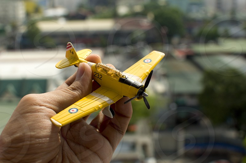 Holding a yellow vintage toy airplane photo