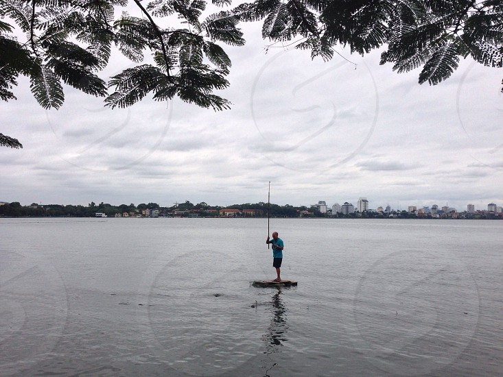 person standing on boat on body of water photo