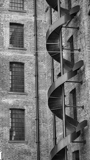 metal spiral stairs on concrete building in grayscale photography photo