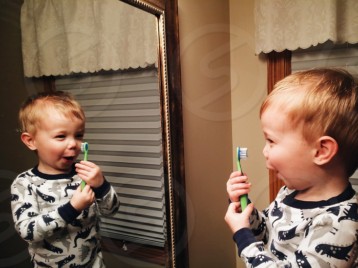 Young boy playfully brushing teeth photo