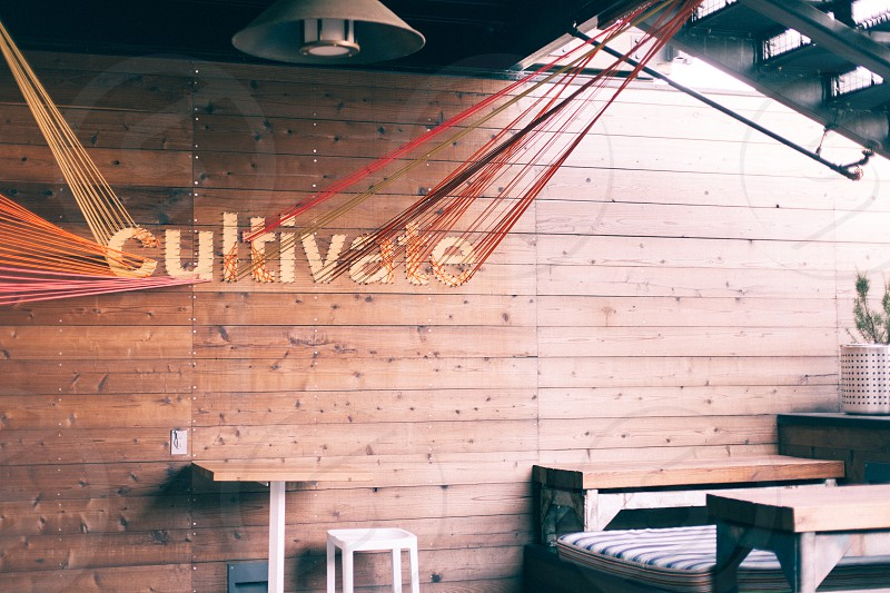 white wooden stool near brown and white wooden table below cultivate sign on brown wooden wall photo