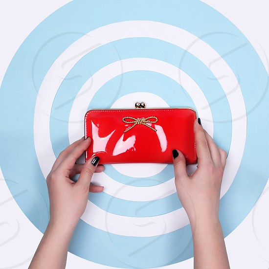 Beautiful unusual romantic red purse holding a hand with black nails on a blue and white circles background pop art photo