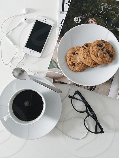Working space table desk breakfast meal food white minimal minimalist minimalistic lunch coffee time white desk white background cookies coffee phone glasses  photo