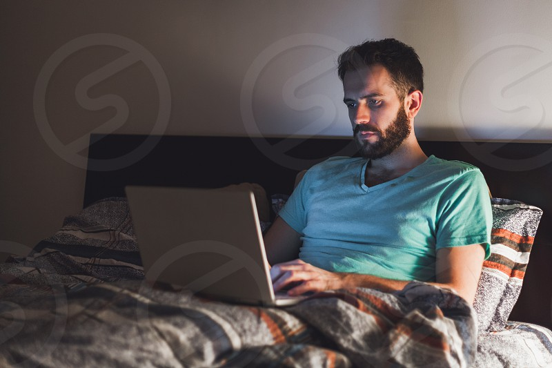 Young man working late in bed on a laptop photo