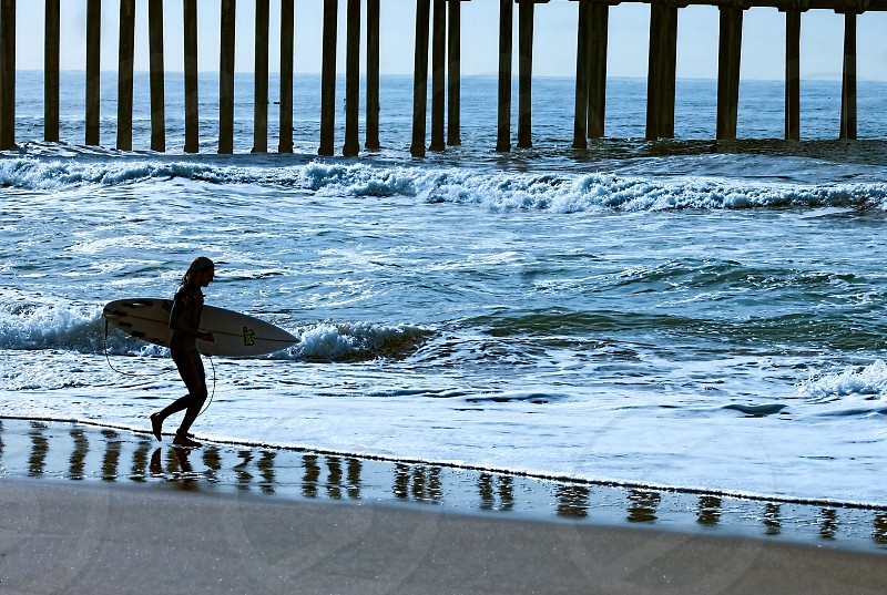 Silhouette of a female surfer holding her surfboard walking along the sand on the reflection of the pylons of a pier. photo