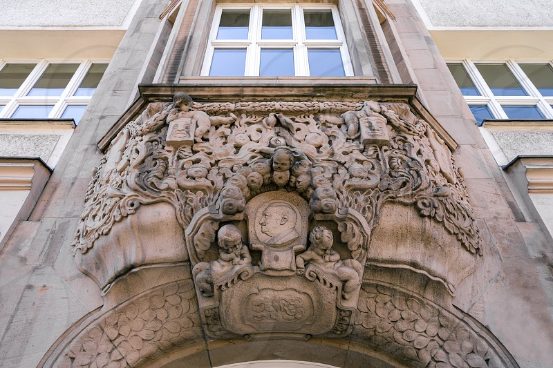 Detailed sculptural decoration of the gable and arched entrance in the Baroque style. Figures carved in stones adorn the entrance of a building with historical details in the city of Berlin. photo