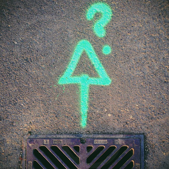 green arrow and question mark printed grey concrete floor photo