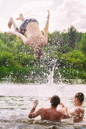 Jumping with friends for fun. Summer youngsters fun river. photo