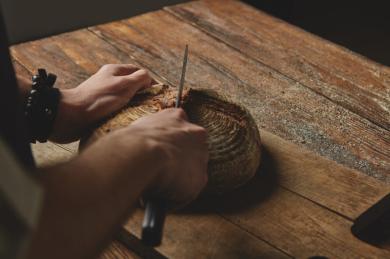 Man baker cutting a knife bread on a wooden cutting board on old wooden background photo