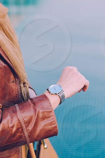 Elegant woman wearing silver wristwatch and brown leather coat holding leather brown handbag. Standing in front of blue background photo