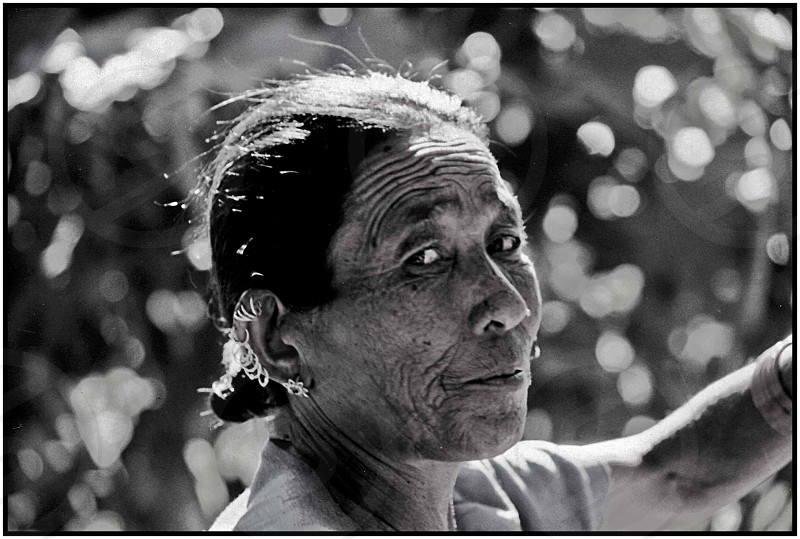 Woman elderly stare glare eyes candid portraiture Nepal black&white shot on film pierced earrings photo