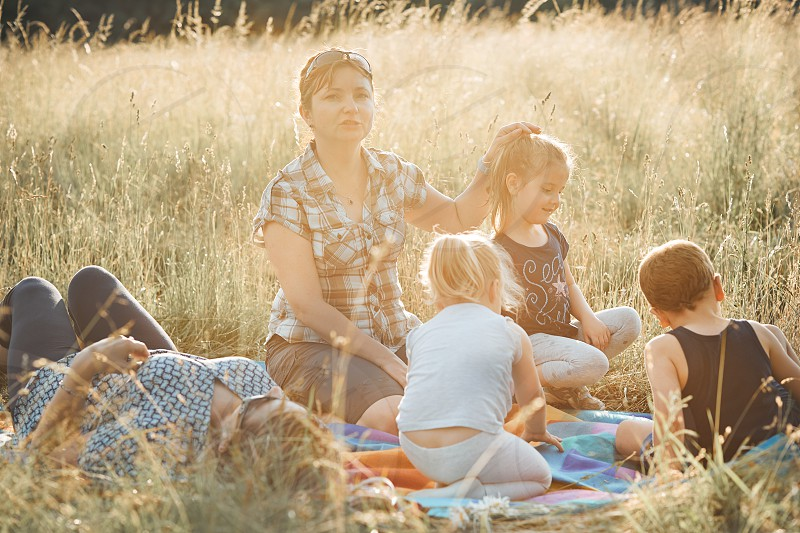 Family spending time together on a meadow close to nature. Parents and children sitting and playing on a blanket on grass. Candid people real moments authentic situations photo