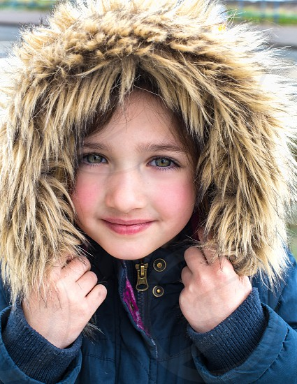 Close-up of pretty little girl face framed by faux fir hood on winter coat. photo
