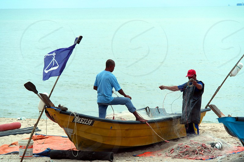 2 people standing near brown wooden boat with blue flag beside a sea during daytime photo
