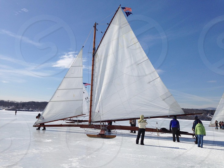 people standing near sailboats under blue sky photo