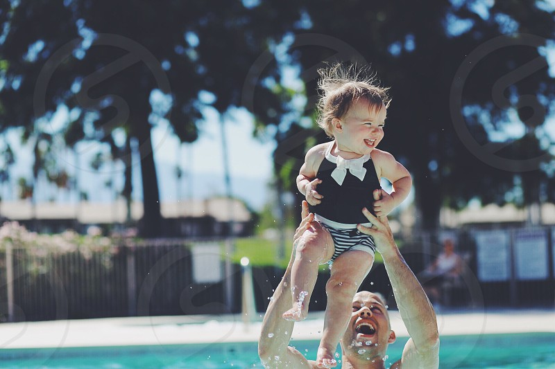 Uncle having a blast with niece in a pool.  photo